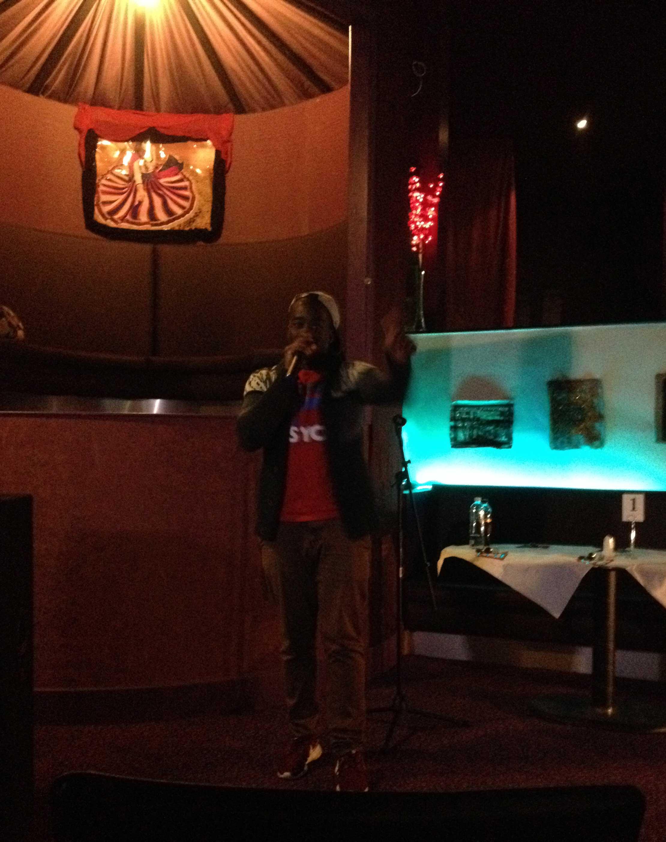 En man som beatboxar i en mikrofon på en mörk klubb.